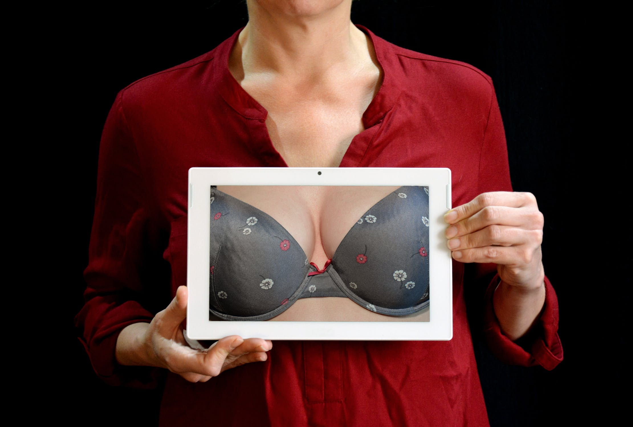 woman holding up image of breasts in a bra after breast reduction surgery