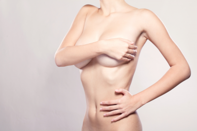 topless woman with slim figure covering breasts