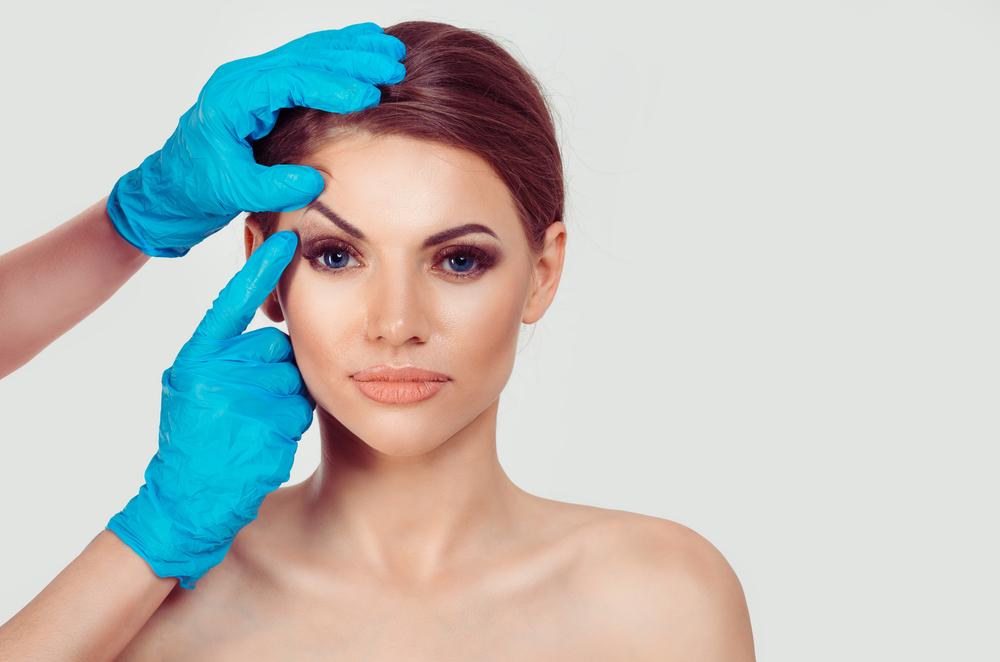 hands with doctor's gloves pushing up woman's eyelids
